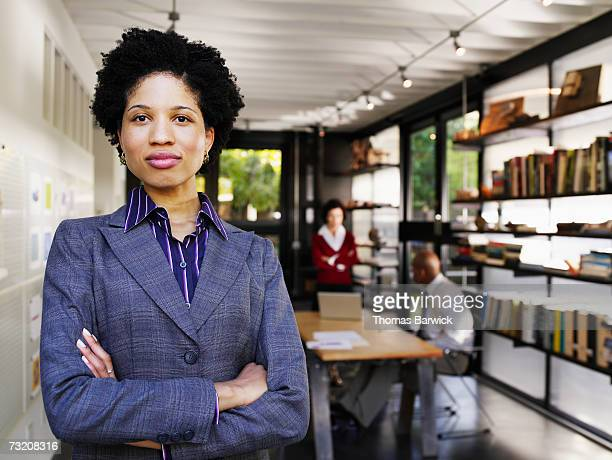 Businesswoman with arms crossed, in office, portrait