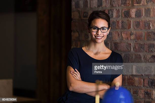 Businesswoman with arms crossed leaning on wall