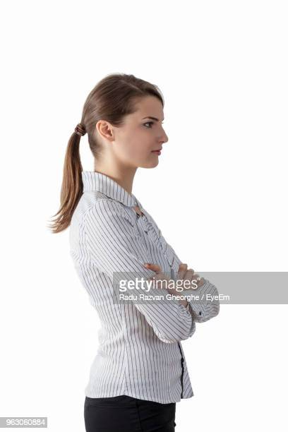 Businesswoman With Arms Crossed Standing Against White Background