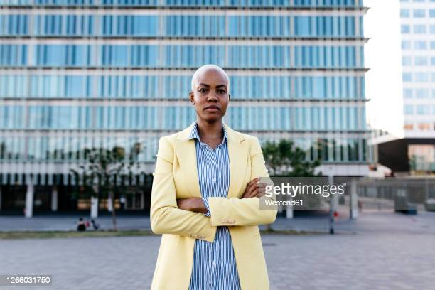 businesswoman with arms crossed standing in city - white hair stock pictures, royalty-free photos & images