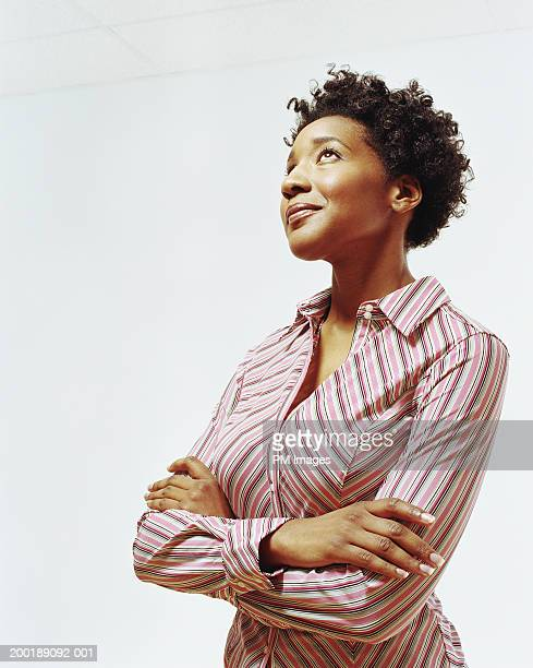 Businesswoman with arms folded looking upward, smiling