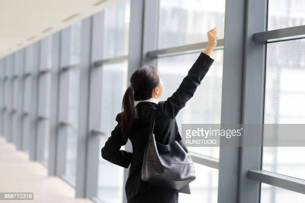 Businesswoman with arms raised at office window