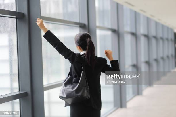 Businesswoman with arms raised in corridor