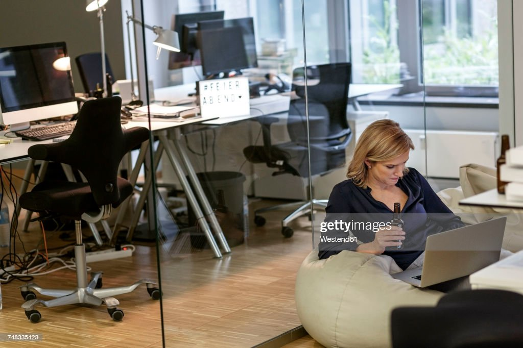 Businesswoman with beer bottle and laptop in office : Stock-Foto