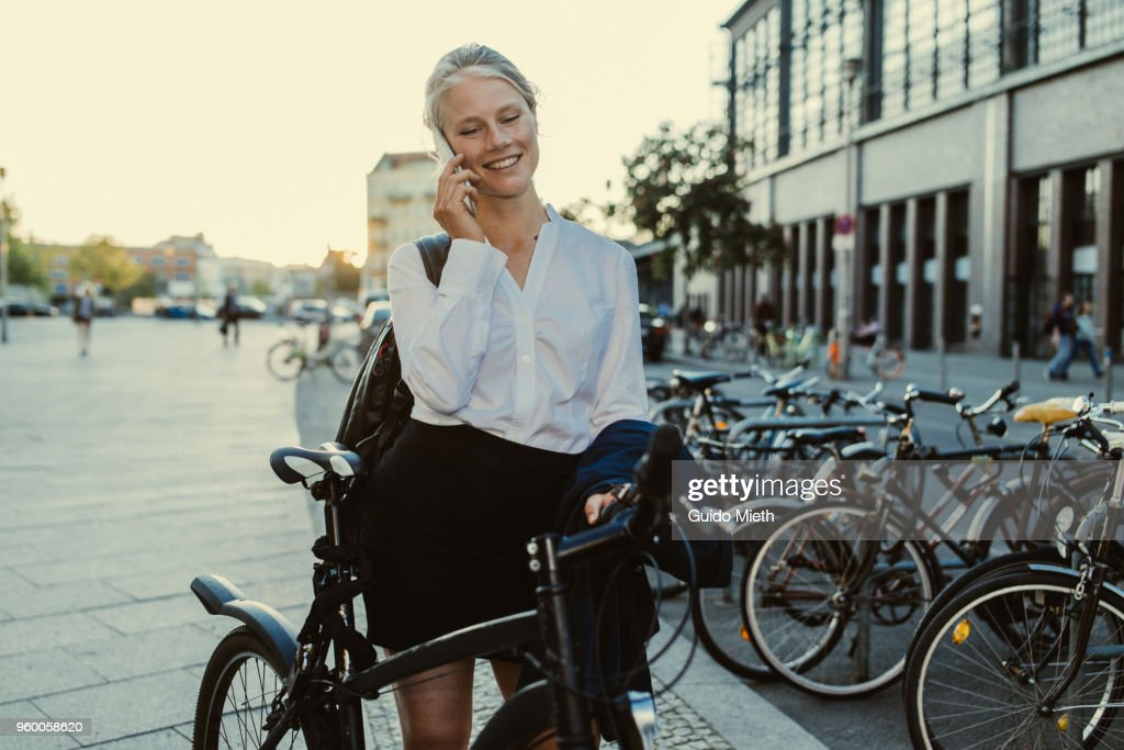 Businesswoman with bicycle using smartphone. : Stock-Foto