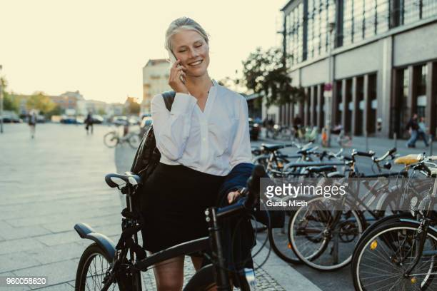 Businesswoman with bicycle using smartphone.