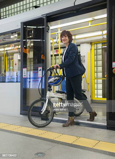 businesswoman with bike leaving subway train