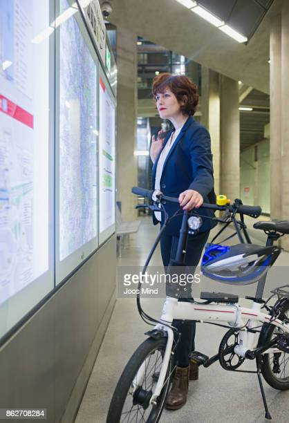 businesswoman with bike reading timetable at subway station