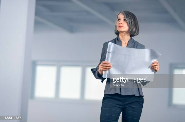 businesswoman with blueprint standing in office - bobbed hair stock pictures, royalty-free photos & images