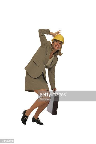 Businesswoman with briefcase and hardhat ducking