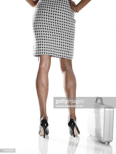 businesswoman with briefcase (low section, rear view) - black skirt stock photos and pictures