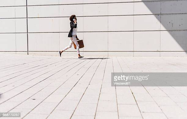 businesswoman with briefcase running while telephoning with smartphone - woman hurry stockfoto's en -beelden