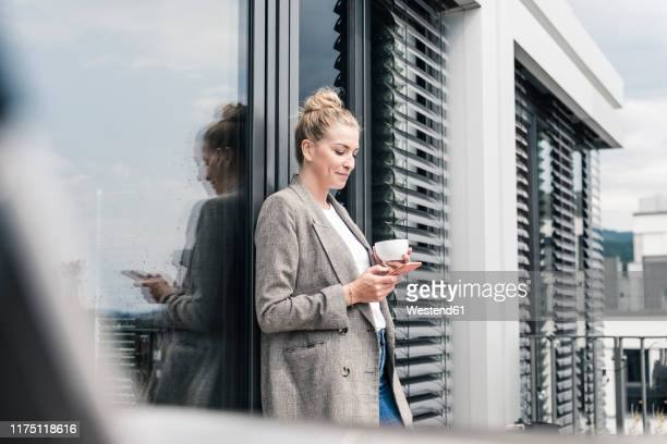 businesswoman with cell phone and coffee cup standing on roof terrace - donne di età media foto e immagini stock