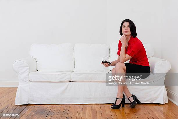 Businesswoman with cell phone on sofa