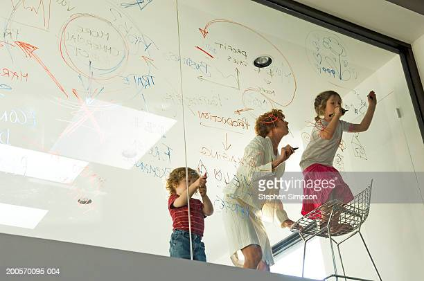Businesswoman with children (4-7) writing on glass