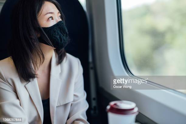 businesswoman with cloth mask looking through the train window - railway station stock pictures, royalty-free photos & images