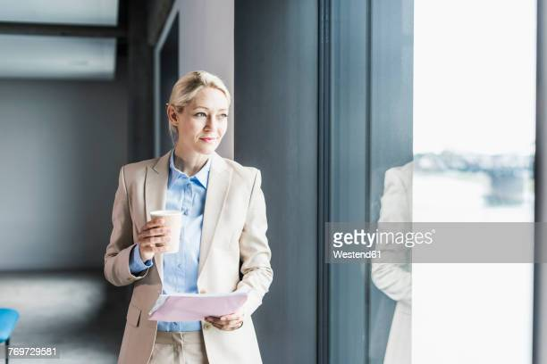 businesswoman with coffee and documents at the window - natuurlijk fenomeen stockfoto's en -beelden