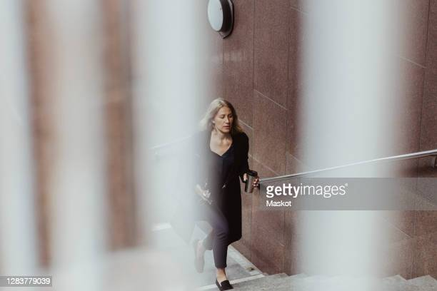 businesswoman with coffee cup climbing staircase in city - woman hurry stockfoto's en -beelden