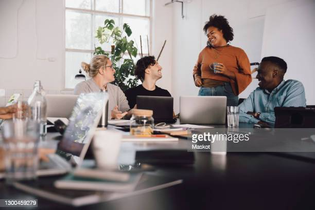 businesswoman with coffee cup discussing with colleagues in office meeting - vanguardians stock pictures, royalty-free photos & images