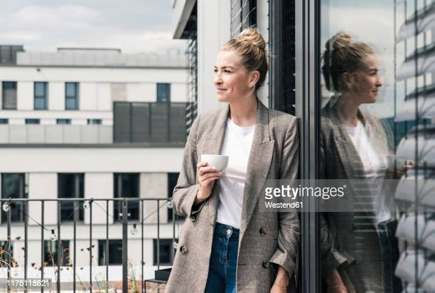 businesswoman with coffee cup standing on roof terrace - elegante kleidung stock-fotos und bilder