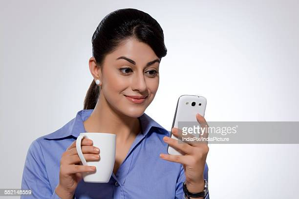 Businesswoman with coffee mug smiling while reading text message on smart phone over gray background
