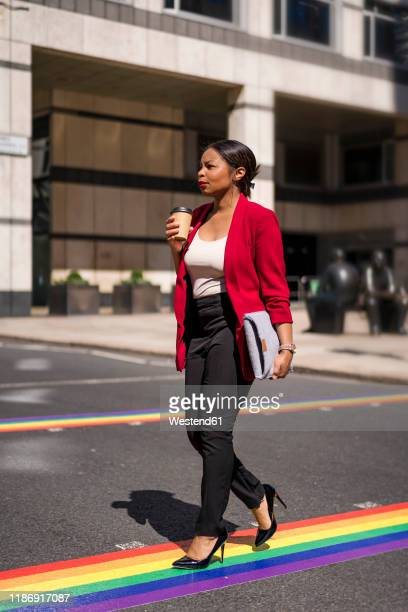 businesswoman with coffee to go and laptop bag crossing the street on lgbt stripes, london, uk - striped blazer stock pictures, royalty-free photos & images