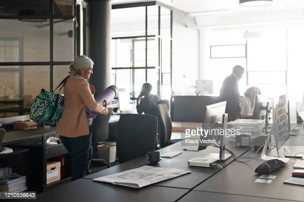 businesswoman with colleagues at modern workplace - brown purse stock pictures, royalty-free photos & images
