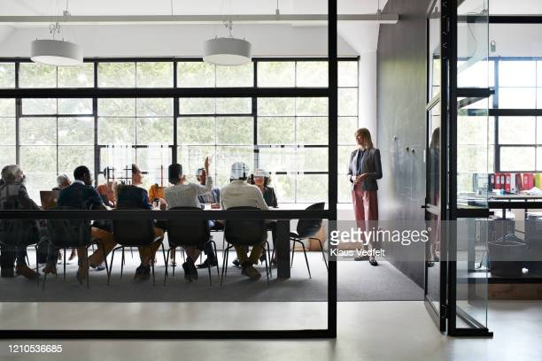 businesswoman with colleagues in board room - leadership stock pictures, royalty-free photos & images