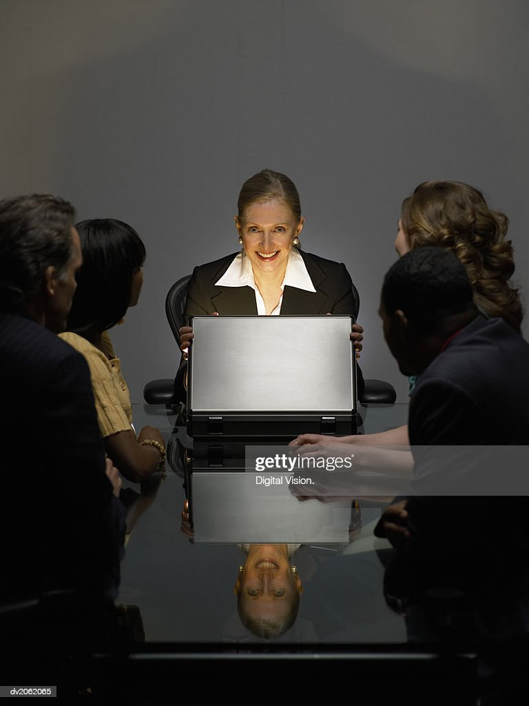 Businesswoman With Colleagues Sitting in a Dark Office Opening a Bright Briefcase : Stock Photo