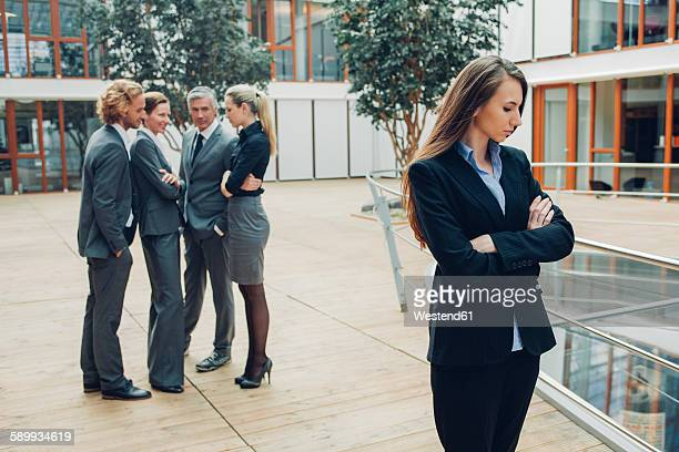 businesswoman with crossed arms, excluded from group of business people - ausschluss stock-fotos und bilder