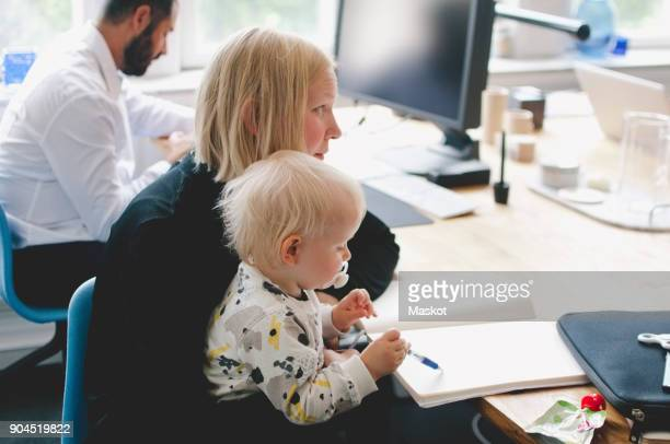 Businesswoman with daughter writing in book at table in creative office