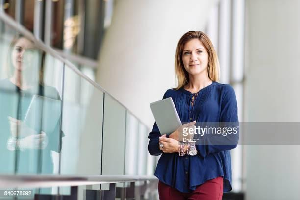 Businesswoman with digital tablet in modern interior