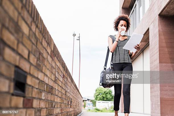 Businesswoman with documents and coffee to go