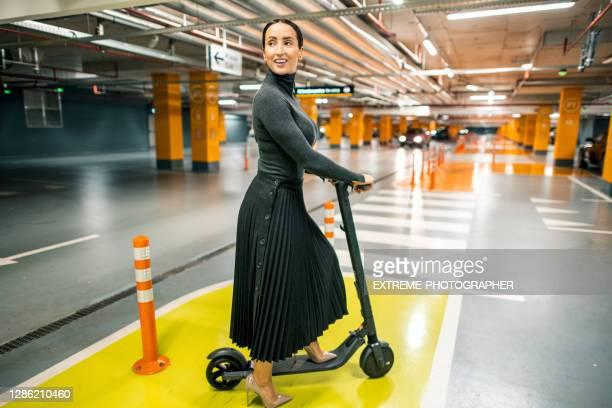 onderneemster met e-scooter in de parkeergarage van haar werkplek - rok stockfoto's en -beelden