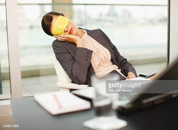 Businesswoman with eye mask sleeping in office