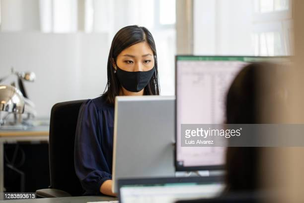 businesswoman with face mask busy working at her desk - protective workwear stock pictures, royalty-free photos & images