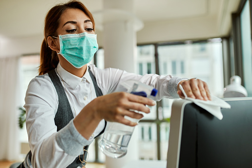 Businesswoman with face mask disinfecting desktop PC in the office. 1220006108