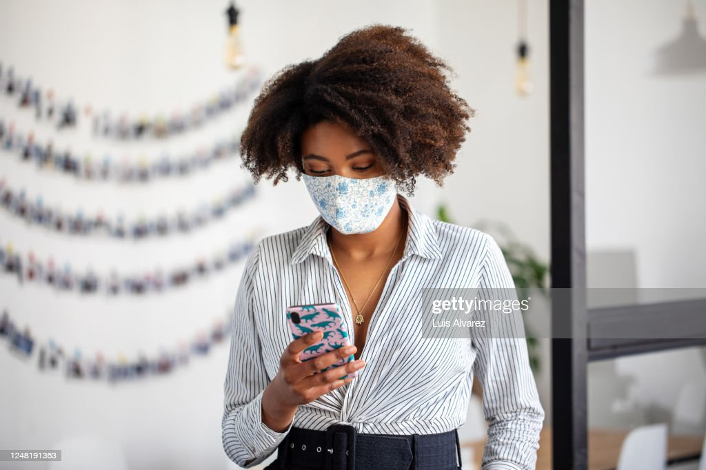 Businesswoman with face mask using mobile phone in office : Stockfoto