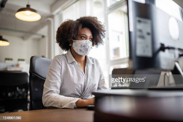businesswoman with face mask working at her desk - coronavirus stock pictures, royalty-free photos & images