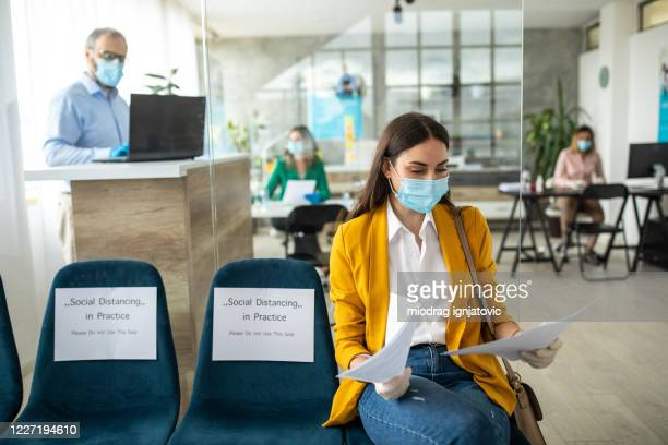 businesswoman with face protective mask in bank waiting room - new normal stock pictures, royalty-free photos & images