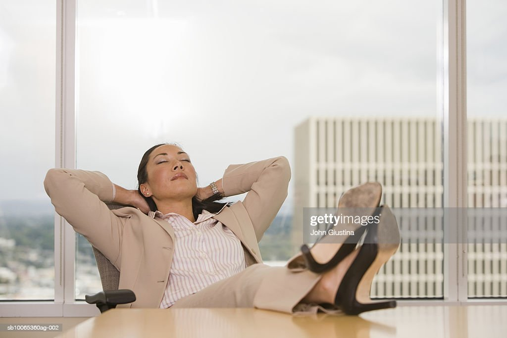 Businesswoman with feet on desk, looking away, eyes closed : Foto stock