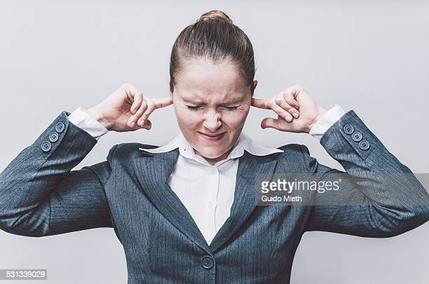 Businesswoman with finger in ears.