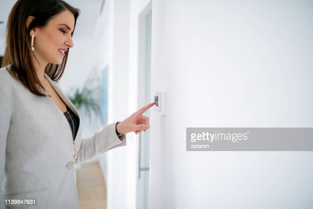 businesswoman with finger on light switch - turning on or off stock pictures, royalty-free photos & images