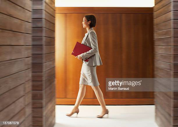 Businesswoman with folder walking in office corridor