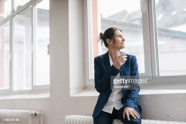 Businesswoman with glass of water sitting on radiator in a loft looking through window