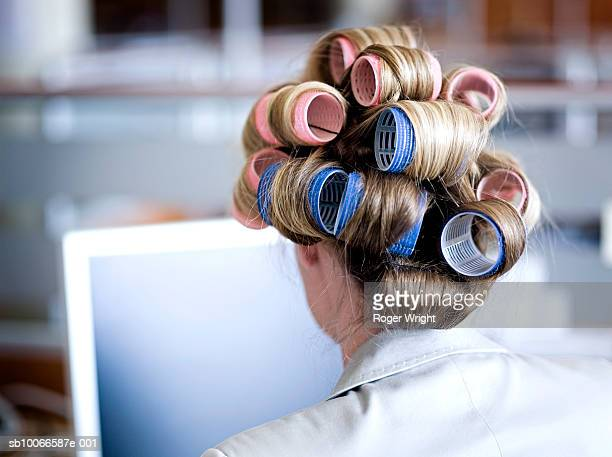 Businesswoman with hair on curlers in office, rear view