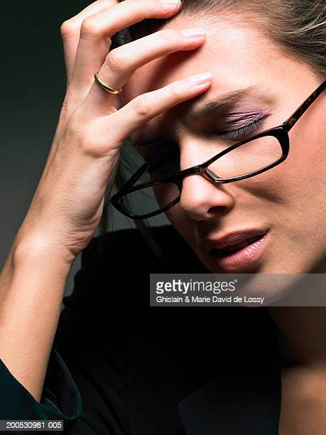 Businesswoman with hand on forehead, wearing glasses, close-up