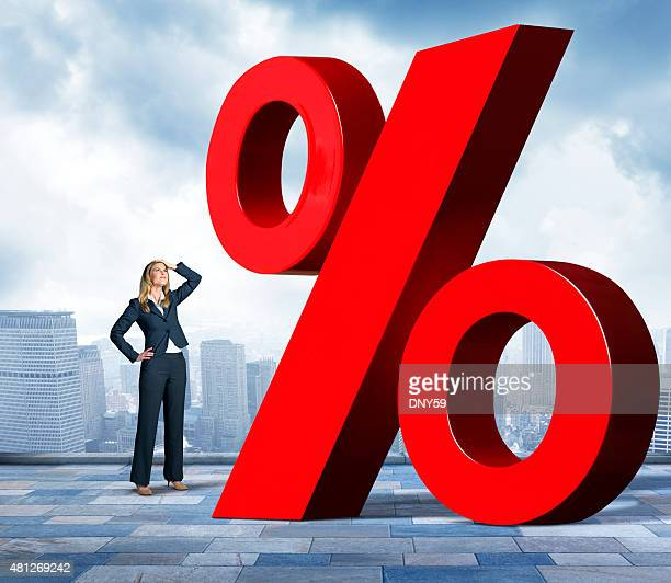 businesswoman with hand on head looking up at percentage sign - interest rate stock pictures, royalty-free photos & images