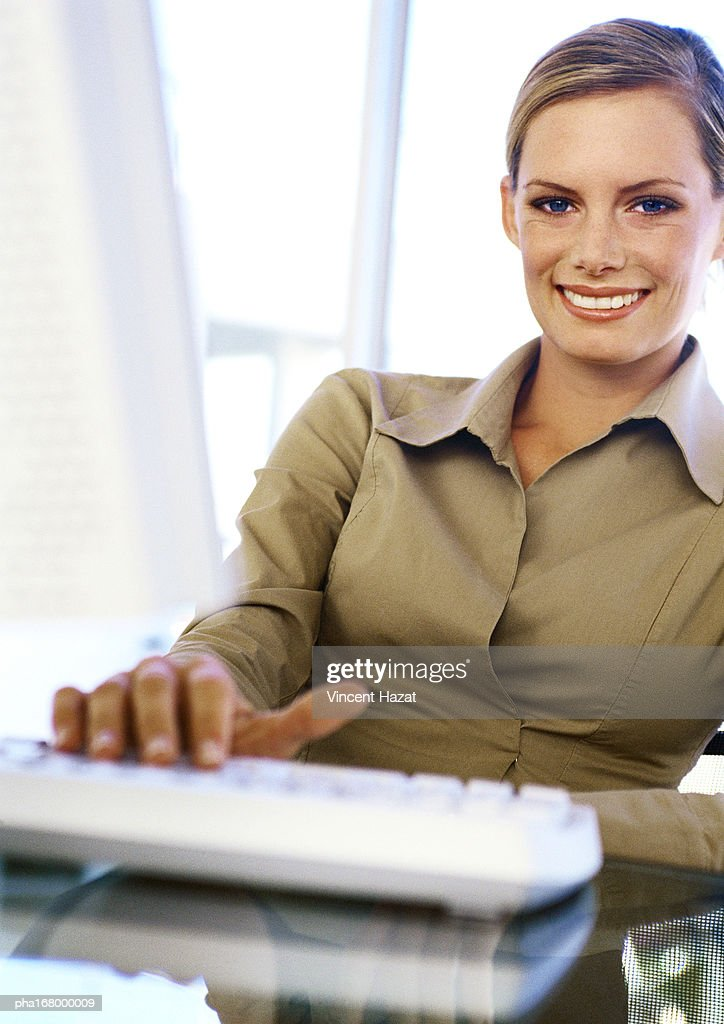 Businesswoman with hand on keyboard, smiling, portrait : Stockfoto