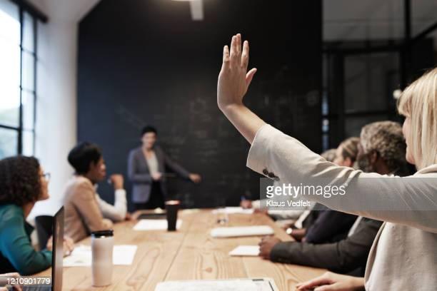 businesswoman with hand raised in conference room - teilnehmen stock-fotos und bilder